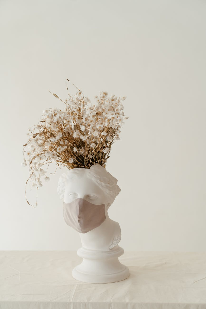 white and yellow flowers in white vase